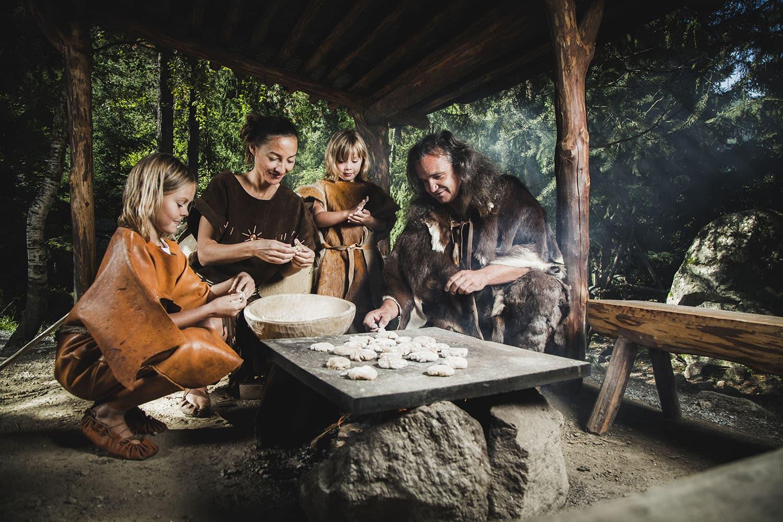 Steinzeitliche Familie beim Brotbacken im Ötzi-Dorf